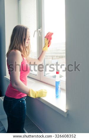 happy young woman housewife washes a window