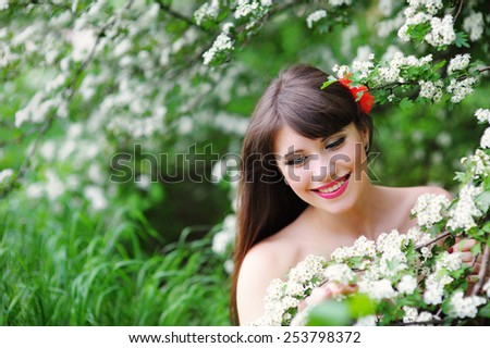 happy young woman in a spring park smelling the flowers. - stock photo