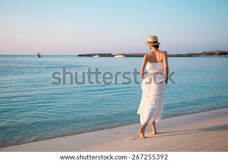 Happy young woman in a white sundress walking by the beach - stock photo