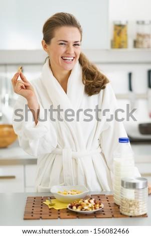 Happy young woman in bathrobe having healthy breakfast - stock photo