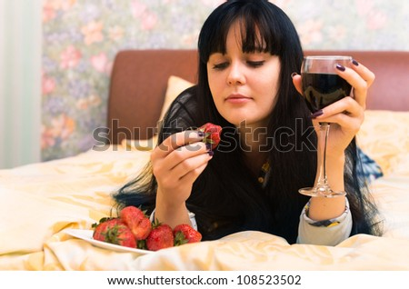 Happy young woman in bed with strawberries and glass of wine - stock photo