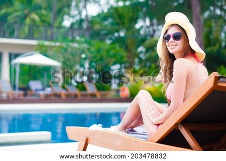 Happy young woman in bikini enjoying her time on chaise-longue luxury pool side - stock photo