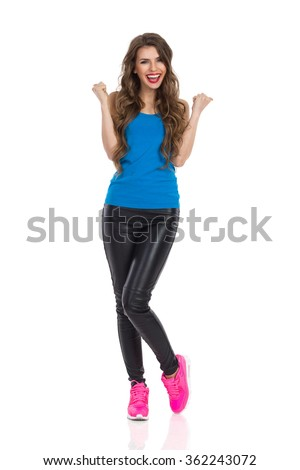 Happy young woman in blue shirt, black leather trousers, and pink sneakers standing with arms raised and shouting. Full length studio shot isolated on white. - stock photo