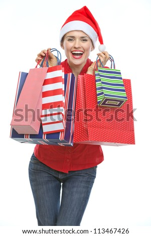 Happy young woman in Christmas hat with shopping bags - stock photo