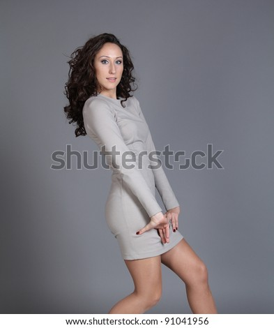 Happy young woman in grey dress. Isolated over grey background.