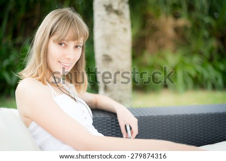 Happy young woman in headphones listening to music outdoor sitting on the sofa with cushions under shed. Palm tree near by and green lawn in background. Holidays and vacation on tropical resort. - stock photo