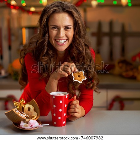 Happy young woman in red dress having snack in christmas decorated kitchen