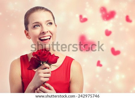 Happy young woman in red dress holding red roses - stock photo