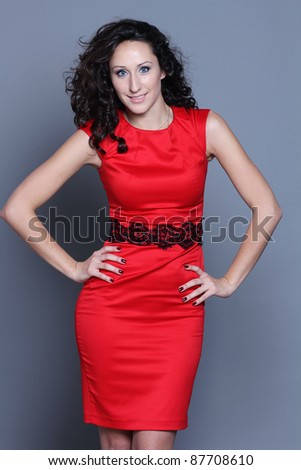 Happy young woman in red dress. Isolated over grey background.