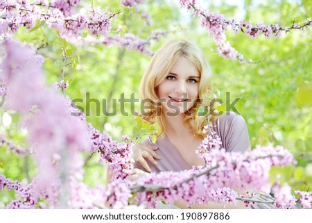 Happy young woman in spring flowers garden - stock photo