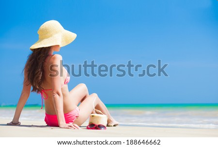 Happy young woman in straw hat and bikini with coconut on the beach - stock photo