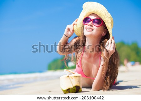 Happy young woman in straw hat on the beach