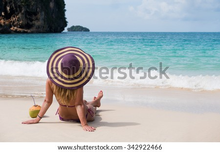Happy young woman in straw hat with  on the beach with a coconut drink - stock photo