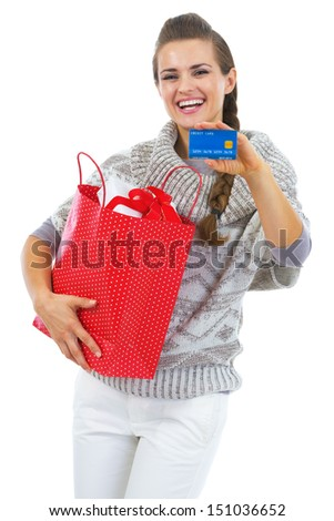 Happy young woman in sweater with christmas shopping bag showing credit card