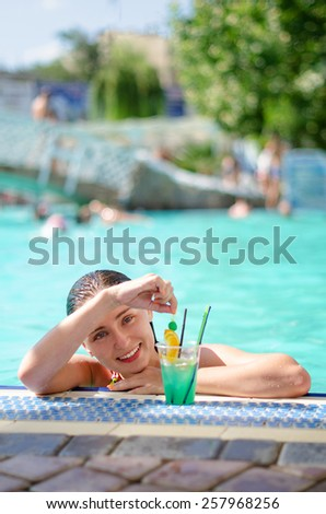 Happy young woman in swimming pool drinking cocktail. Summer vacation in resort by the poolside. Active lifestyle - stock photo