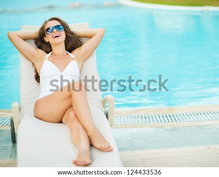 Happy young woman in swimsuit laying on chaise-longue poolside - stock photo