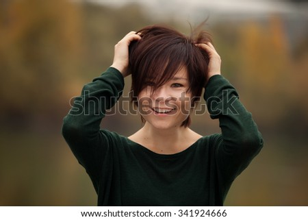 Happy young woman in the autumn park - stock photo