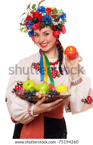Happy young woman in the Ukrainian national clothes with fruit - stock photo