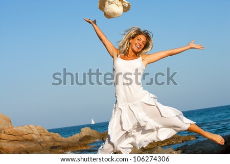 Happy young woman in white dress jumping on beach. - stock photo