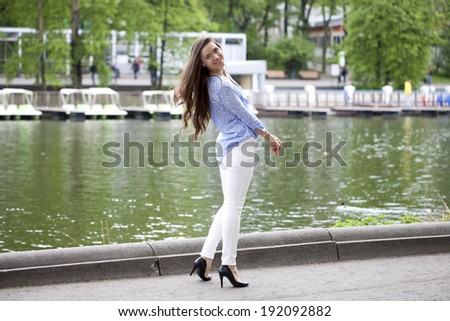 Happy young woman in white pants and a blue shirt walking in the summer park - stock photo