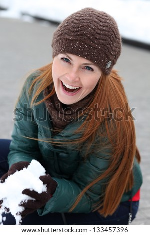 Happy young woman in winter city - stock photo
