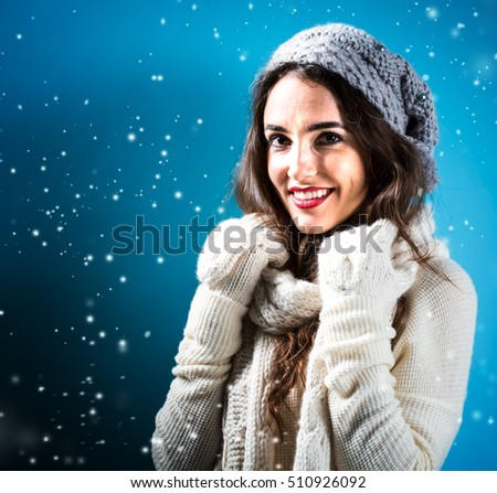 Happy young woman in winter clothes in snowy night