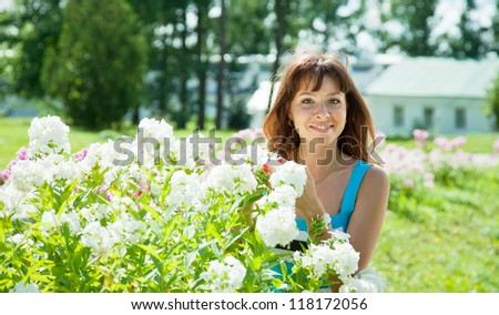Happy young woman in yard gardening with phlox plant