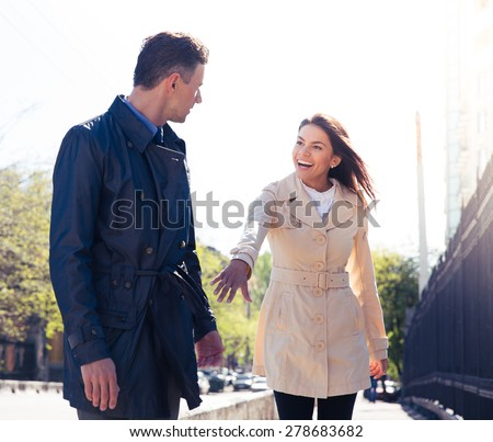 Happy young woman inviting man outdoors - stock photo