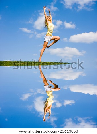Happy young woman is dancing in a field - stock photo