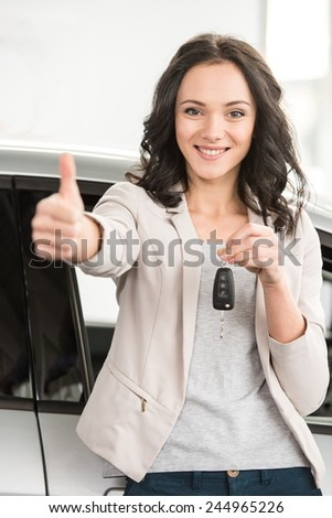 Happy young woman is holding keys to new car and looking at the camera. - stock photo