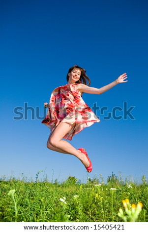 Happy young woman is jumping in a field. In red dress and red shoes. Against the backdrop of blue sky. - stock photo
