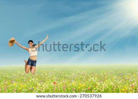Happy young woman is jumping on the park