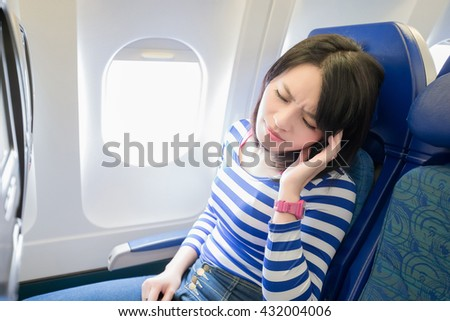 Happy young woman is sitting in the airplane, feel headache, asian - stock photo