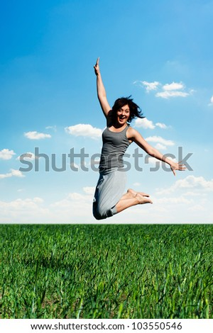 happy young woman jumping at the field at sunny day - stock photo
