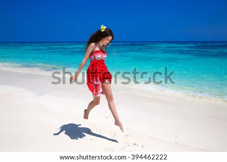 Happy young woman jumping on exotic sea, brunette smiling girl in red dress running on tropical beach with white sand. Enjoyment. Lifestyle. Freedom. Good life. Travel.  - stock photo