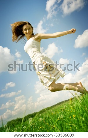 Happy young woman jumping over blue sky - stock photo