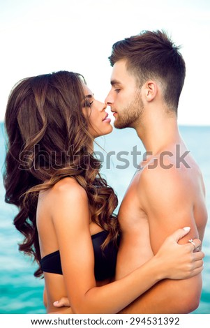 Happy young woman kissing her handsome boyfriend,enjoy their summer vacation on amazing beach,lifestyle portray of stylish hipster couple in love.Enjoying Beautiful Sunset at the Beach,sensual couple - stock photo