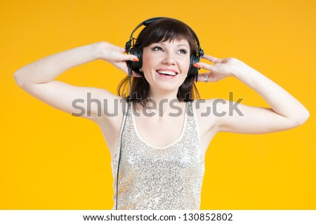 Happy young woman listening to music in headphones - stock photo