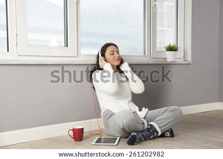 Happy young woman listening to music while sitting on the floor at home.