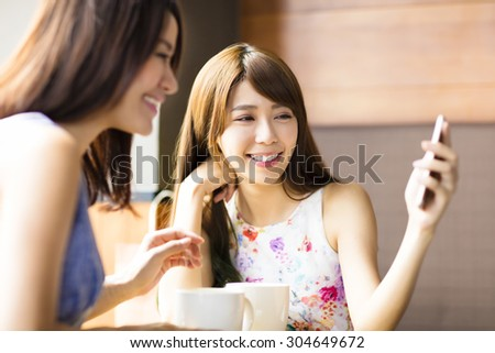 happy young woman looking at phone in coffee shop - stock photo