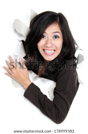 Happy young woman looking through a hole. Isolated on white background - stock photo