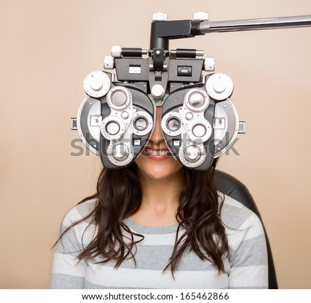 Happy young woman looking through phoropter during eye exam - stock photo
