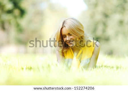Happy young woman lying on grass - stock photo