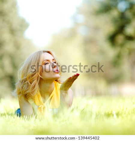 Happy young woman lying on grass and blowing kiss - stock photo