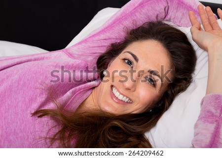 happy young woman lying on her bed - stock photo