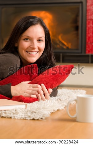 Happy young woman lying on rug by fireplace home living - stock photo
