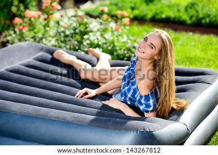 Happy young woman lying on the mattress in the garden - stock photo