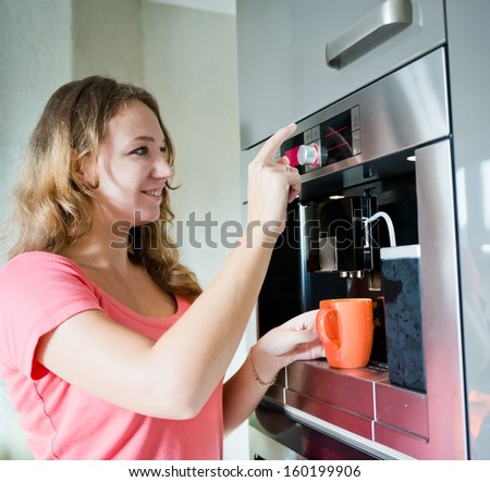 Happy young woman making coffee cup machine kitchen interior