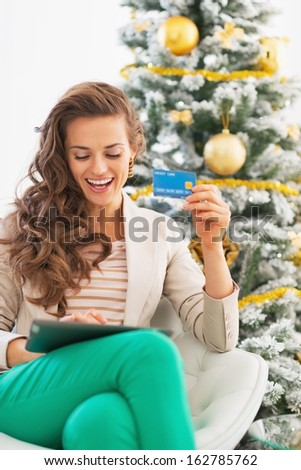 Happy young woman making online shopping with tablet pc near christmas tree - stock photo