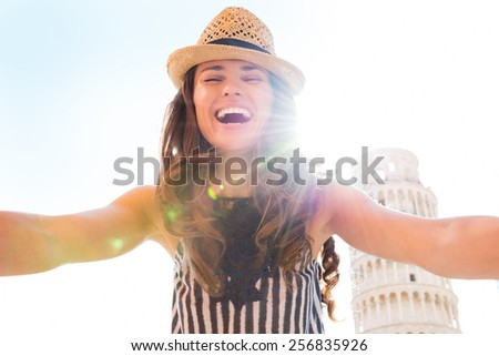 Happy young woman making selfie in front of leaning tower of pisa, tuscany, italy - stock photo